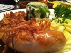 German veal sausage with mashed potatoes and a fat stack of broccoli and cheese.