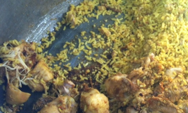 Scraping the bottom of a giant boiler of biryani by 9am