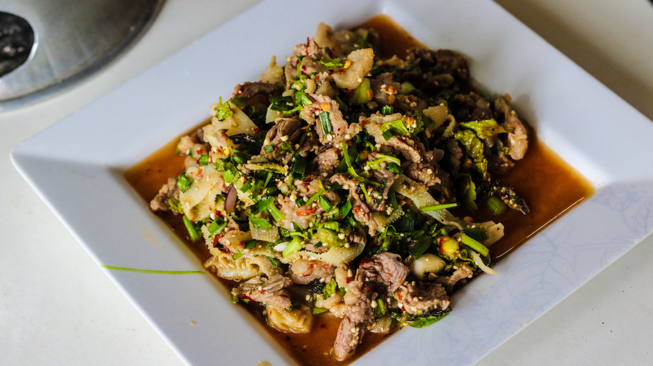 Amazing recipe of Laap today including fresh herbs, rice powder, and thin slices of reticulum, which is a cow stomach